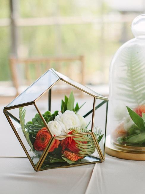 terrrarium w szklanym wazonie z czerwonych i białych kwiatów
