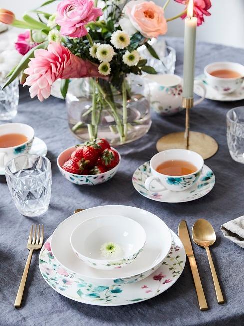 wiosenny stół z kolorową zastawą w kwiaty i dużym bukietem w wazonie