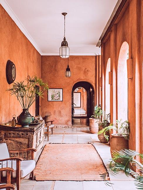 Duży korytarz pomalowany na kolor terkaoty w dużej śródziemnomorskiej willi z łukowymi przejściami