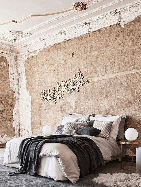 Sypialnia w kamienicy z obnażoną ścianą betonową