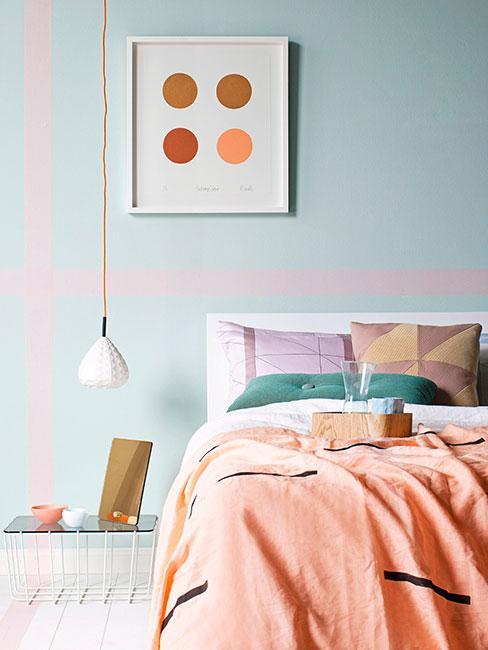 Jasna pastelowa sypialnia z błękitną ścianą i jasnopomarańczową pościelą