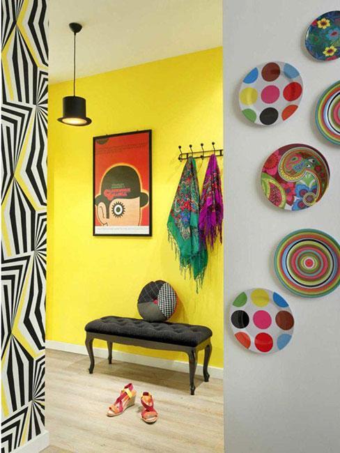 Kolorowy korytarz z żółtą ścianą, kolrowym obrazem i pstrokatymi talerzami na ścianie