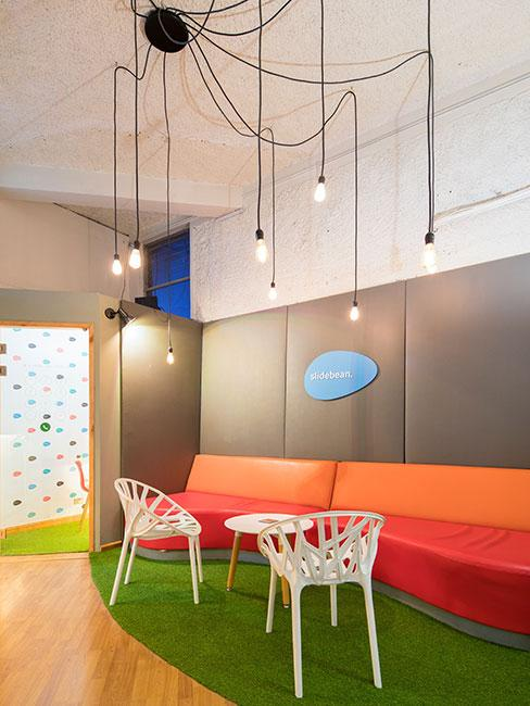 Nowoczesny salon z wiszącymi lampami na długich kablach, pomarańczową ścianą i sztuczną trawą