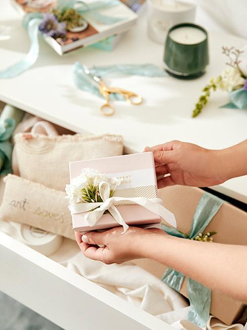 Pięknie zapakowany mały prezent w pastelowych kolorach z małym kwiatem