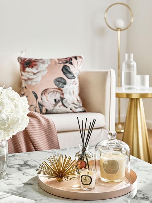 Kącik glamour w salonie z dekoracjami zapachowymi i różową kwiatową poduszką w tle