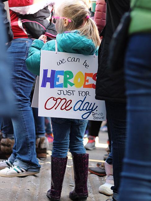 Mała dziewczynka na demonstracji z napisem We can be heroes just for one day