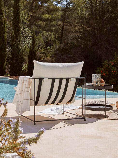 Fotel i stolik ustawione na brzegu basenu