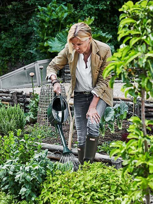 Kobieta podlewająca rośliny w ogrodzie
