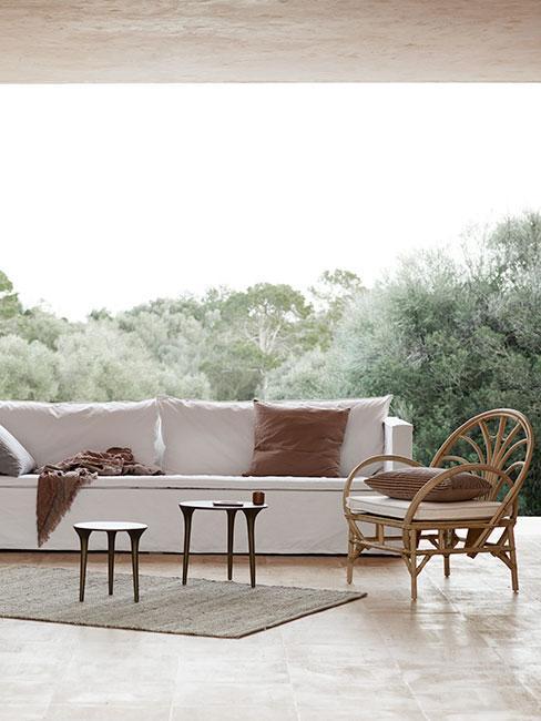Duża baiła sofa obok fotelu rattanowego na tarasie