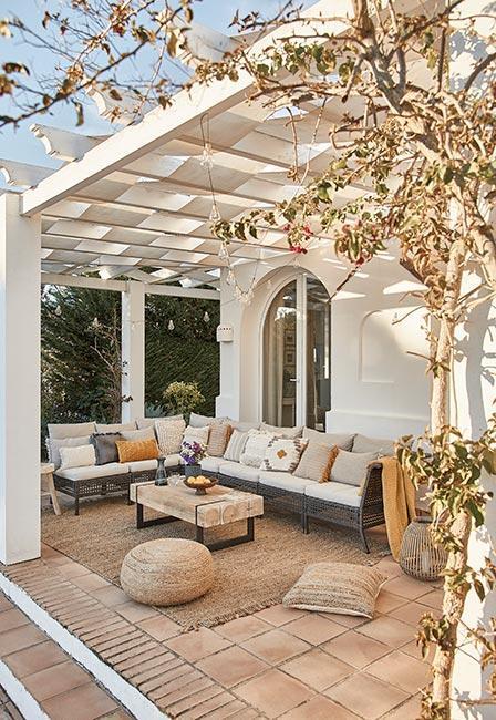 Duża szara sofa obok pufy z juty na śródziemnomorskim tarasie