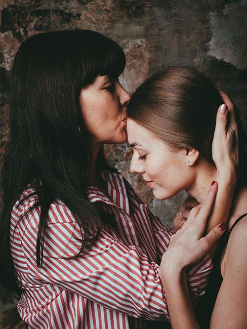 Matka całująca dorosłą córkę w czoło