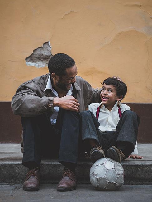 Czarnoskóry mężczyna suiedzący na krawężniku z chłopcem