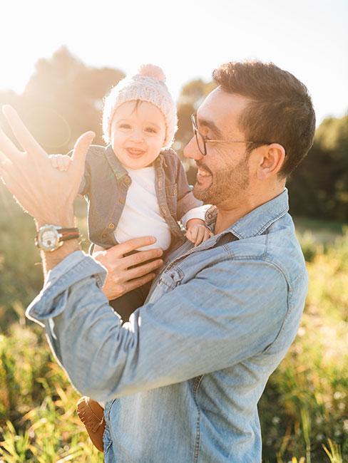 uśmiechnięty młody ężczyzny w jeansowej kurtce z małym dzieckiem
