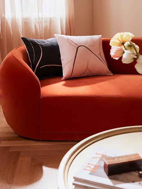 Pomarańczowa obła sofa z poduszkami z motywami kobiet