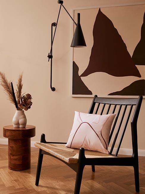 Krzesło z poduszką z motywem ciała kobiety obok stolika z wazonem w kształcie kobiety