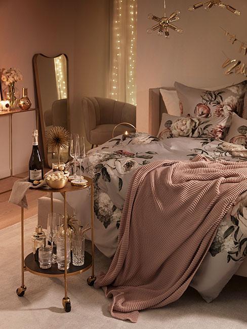 Romantyczna przytulna kobieca sypilania w różu i popielu z szampanem na złotym stoliku i kwiecistą pościelą