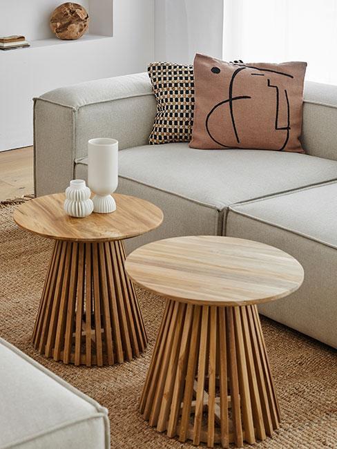 Ażurowe drewnaine stoliki na tle sofy z lnu