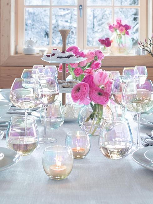 Tęczowe szklanki na stole z różowymi kwiatami