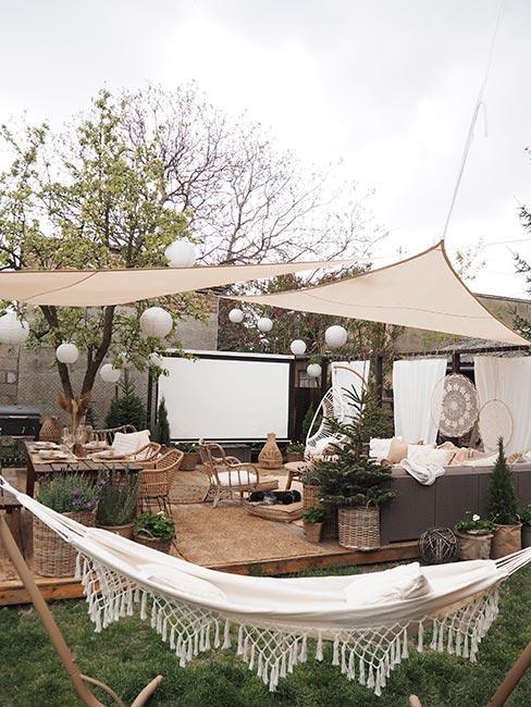 Kino w ogrodzie z lampionami i parasolami i dekoracjami w stylu boho
