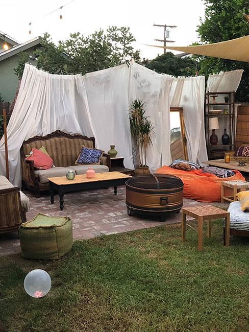 Przytulny ogród z meblami vintage i zasłonami z prześcieradeł