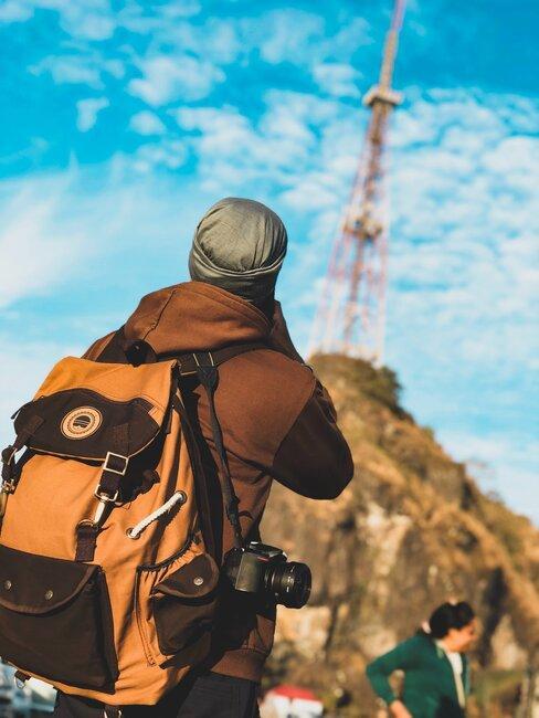 Osoba z plecakiem wspinająca się pod górę
