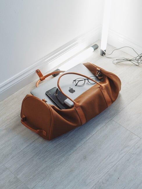 otwarta skórzana torba podróżna na podłodze z komputerem