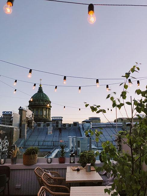 Taras na dachu w dużym mieście, kilka roślin, lampki