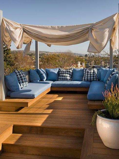 Kanapa z niebieskimi poduszkami stojąca na tarasie