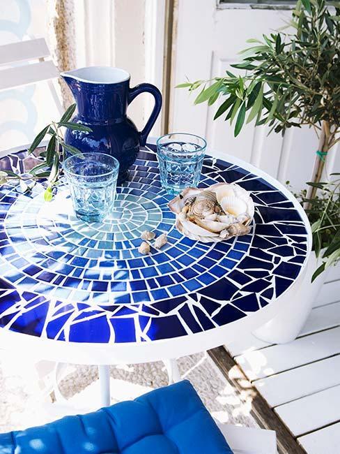 niebieski stolik ogrodowy z blekitnymi naczyniami w stylu greckim