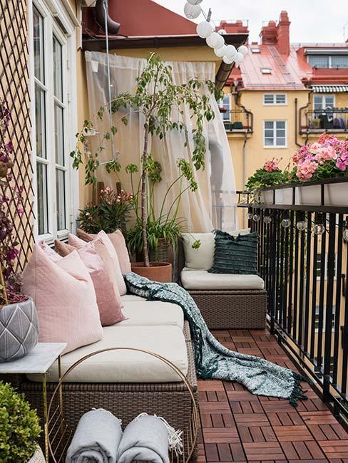 przytulny balkon z różowymi poduszkami i rattanową ławką