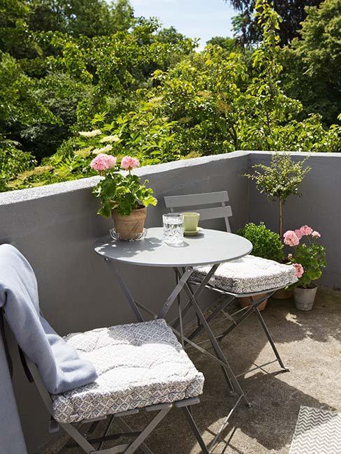 maly szary balkon z metalowymi meblami
