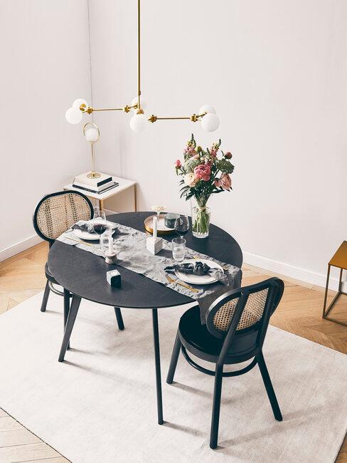 Okrągły stolik i dwa ciemne krzesła
