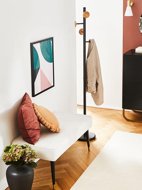 klasyczny elegancki przedpokój z białą ławką boucle i kolorowymi poduszkami