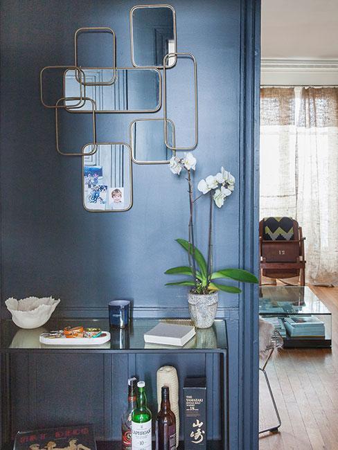 przedpokój z niebieską ścianą i złotymi dekoracjami w stylu art deco