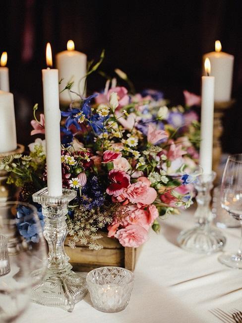 stroik z kwiatów w skrzynce na stole weselnym