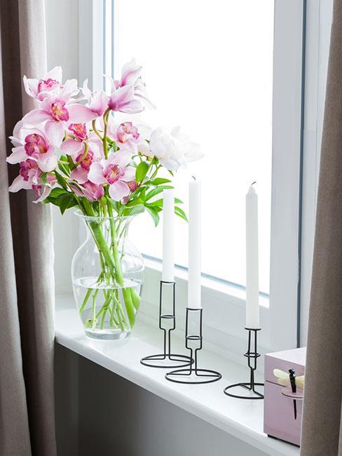różowe kwiaty w szklanym wazonie na oknie obok świeczników