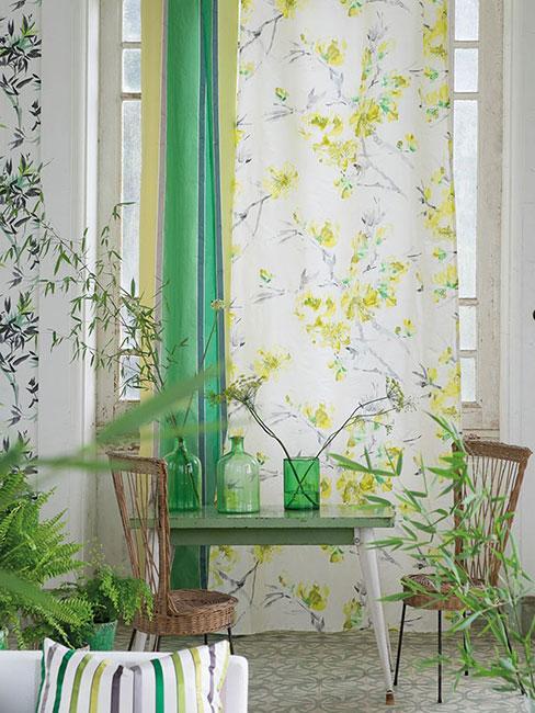 Stolik i wiklinowe krzesła, w tle okno z kwiatową zasłoną