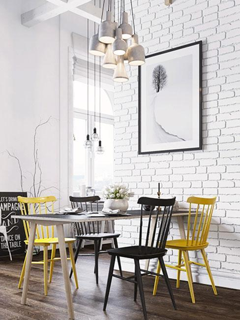 Kolorowe krzesła i mały stolik na tle murowanej ściany