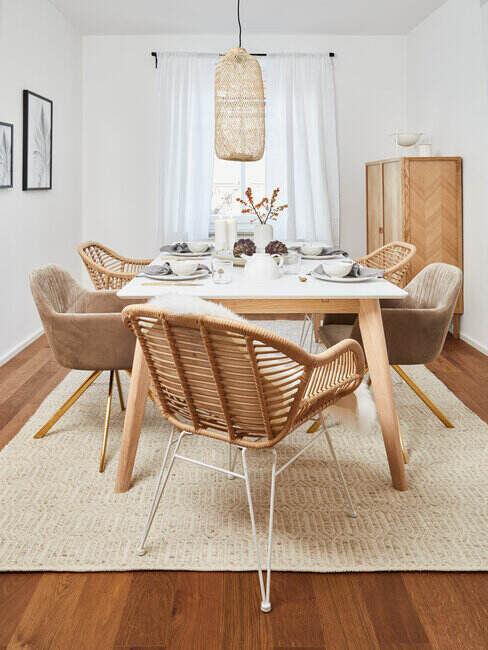 Jadalnia skandynawska, rattanowe krzesła, duży stół i dywan