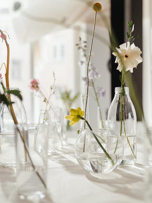 małe szklane wazony z pojedynczymi kwiatami