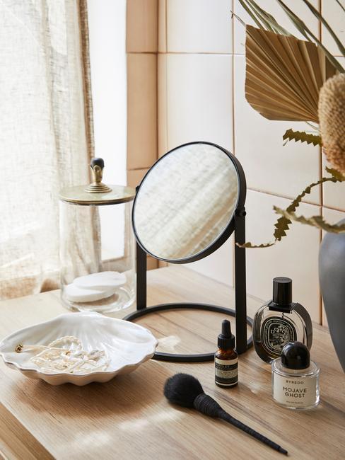 małe czarne lustro w łazience na drewnainej komodzie