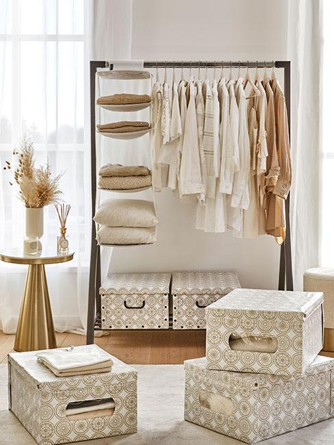 Stojak na ubrania obok pudeł dp przechowywania w jasnych kolorach