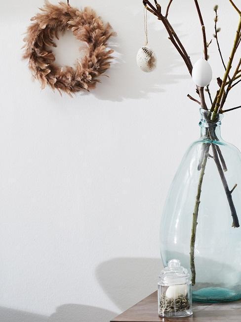 wianek z piór na ścianie obok wazonu z gałązkami wielkanocnymi