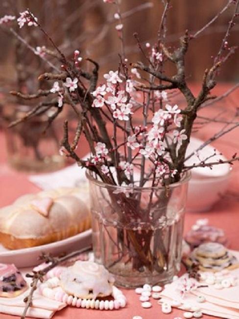 gałązki wiśni w wazonie na stole