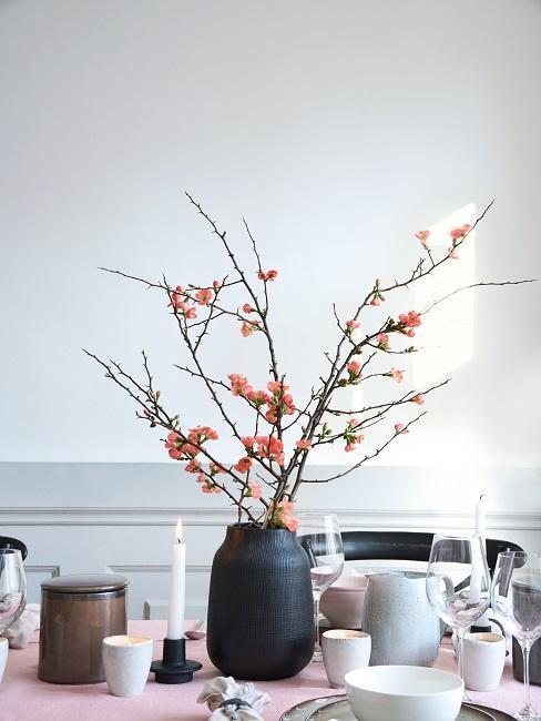 gałązki wiśni w matowym ciemnym wazonie na stole