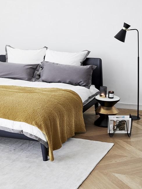 nowoczesna sypialnia z ctarnym łóżkiem, szarą pościelą i żółtą narzutą