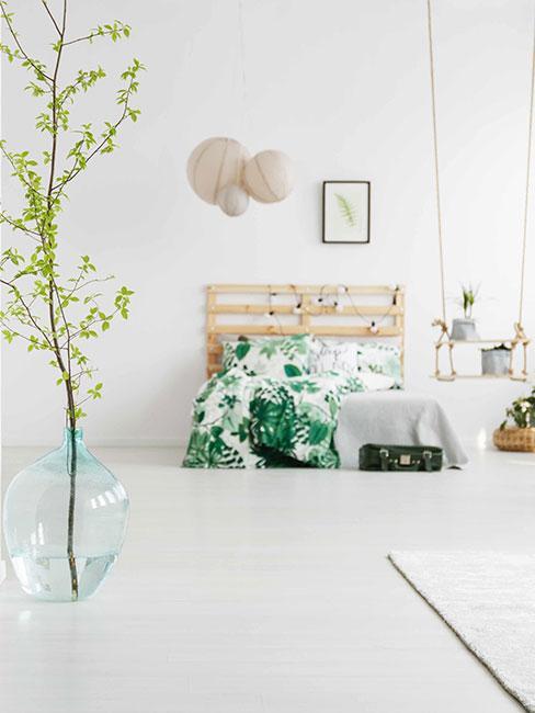 biała minimalistyczna sypialnia z łóżkiem z palet i szklanym wazonem podłogowym z zieloną gałązką
