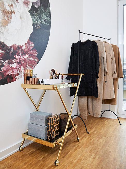 Toaletka na złotym wózku barowym obok stojaka na ubrania