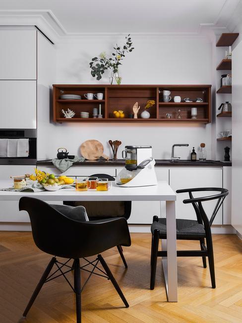 biała kuchnia z jadalnia i czarnymi krzesłami