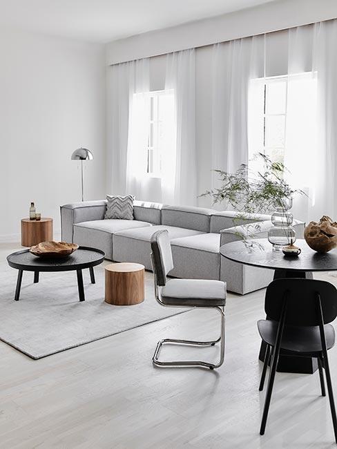 jasny nowoczesny salon z szarą sofą modułową i meblami w drewnie i szkle